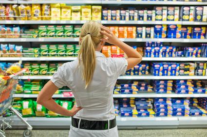 Eine Frau ist mit der großen Auswahl in einem Supermarkt beim Einkauf überfordert.